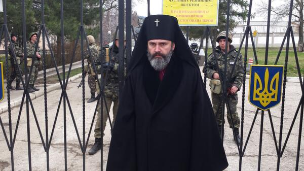 ArchBsp Clement of ukraine orthodox church, stands at gates of surrounded base 'to protect my people'