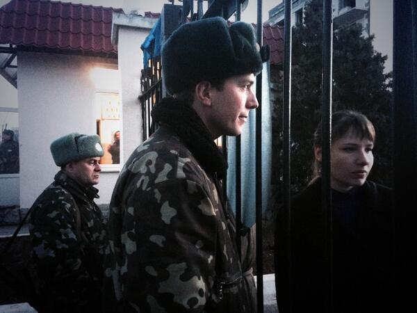 Ukrainian soldiers wave farewell to their loved ones across a gate at air force base in Crimea