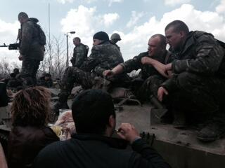 Women at Kramatorsk give Ukraine soldiers bread after they took magazines fro their weapons.