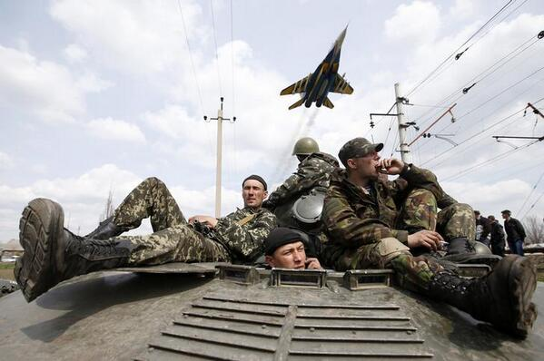 A fighter jet flies above Ukrainian soldiers in Kramatorsk, eastern Ukraine.