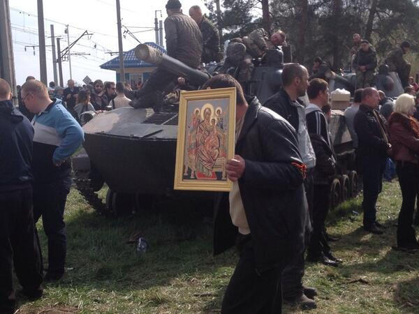 Man with icon helps block ukraine troops and armored vehicles near Kramatorsk