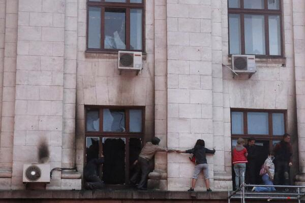 People wait for rescue on a ledge during a fire at Odessa trade union. 40 killed