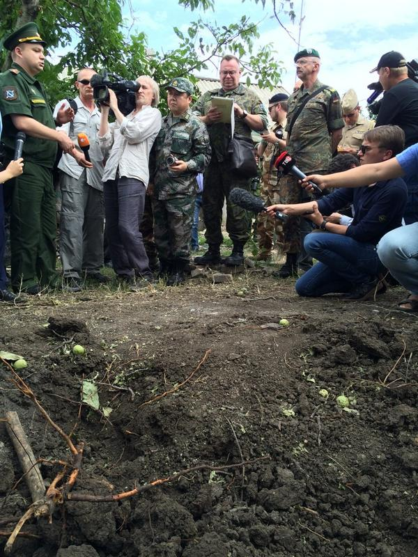 Military attaches from Europe being shown where a Russian man died after a shell came across the border from Ukraine