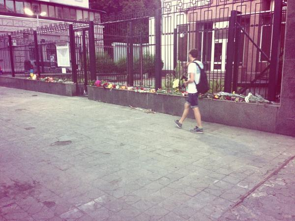 People come to the Russian Embassy to lay flowers in memory of dead in Moscow subway