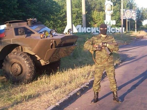 terrorists striking the pose along armour in RUS tricolour in Lysychansk