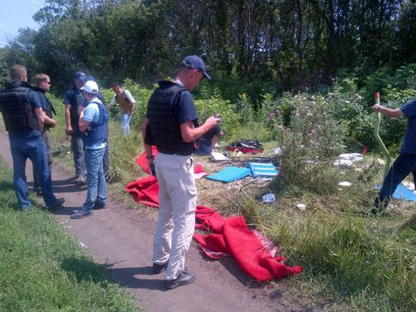 Malaysian officials and OSCE monitors examining the MH17 crash site today