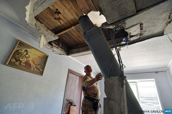 A serviceman inspects an unexploded missile of the type of salvo fire used by pro-Russian militants AFP