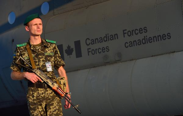Ukrainian soldier stands watch as non-lethal aid from Canada unloaded from RCAF Hercules transport