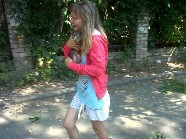 Girl in tears carrying her cat, tries to escape after shells hit her street in center  of Donetsk