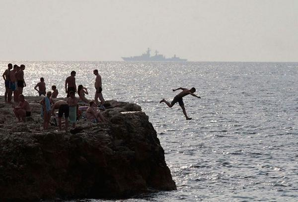 A man jumps into the Black Sea, with a Russian warship in the background, in Sevastopol, Crimea