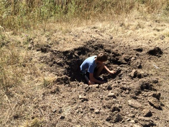 Child plays in a crater in the eastern Ukrainian village of Osykove