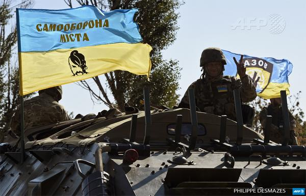 A Ukrainian volunteer makes a victory sign from an armoured vehicle, on the outskirts of Mariupol