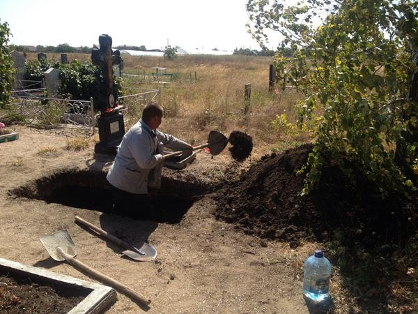 Worker digging a grave for one of the victims of Mariupol shelling on Thursday in the nearby village of Shyrokino