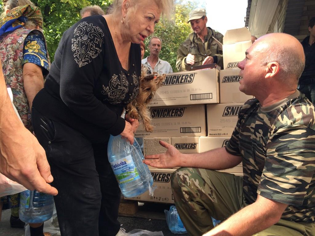 Luhansk residents receive aid, consisting of water, chocolate, toiletries. Aid handed out by camouflaged men