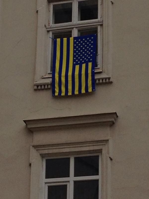 In Lviv, a Ukrainian take on the Stars and Stripes seen hanging from a window in the center of the city