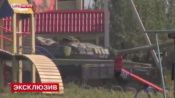 A Russian T-72B1 rolls through an Ukrainian playground in Donetsk city today