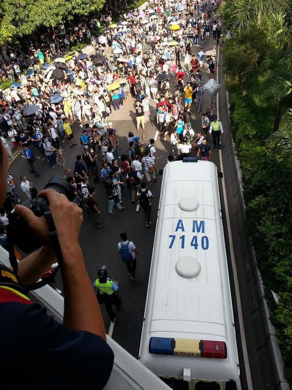 Protesters block police car on Connaught Road while others proceed towards gov. Headquarters in Hong Kong