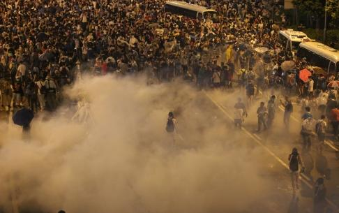 A lone protester stands amid clouds of tear gas as fellow demonstrators are forced back..