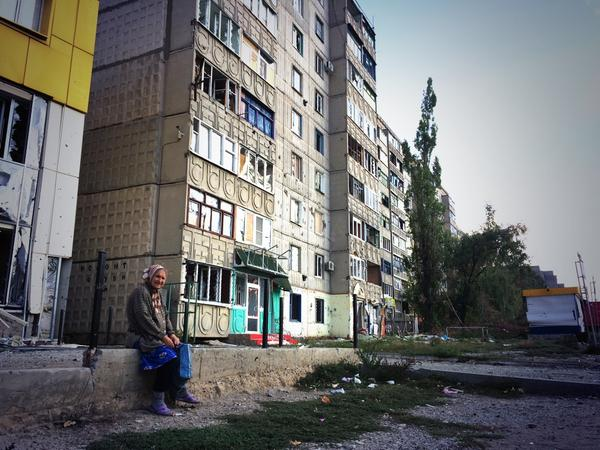 A old woman today in Pervomaisk, eastern Ukraine, sitting down in a residential area shelled a few weeks ago.