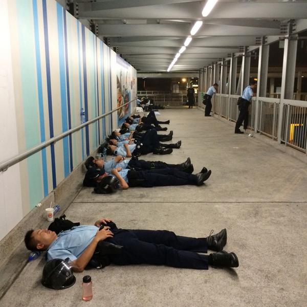 Tired police officers take a break during what has been a long night of protests in Hong Kong