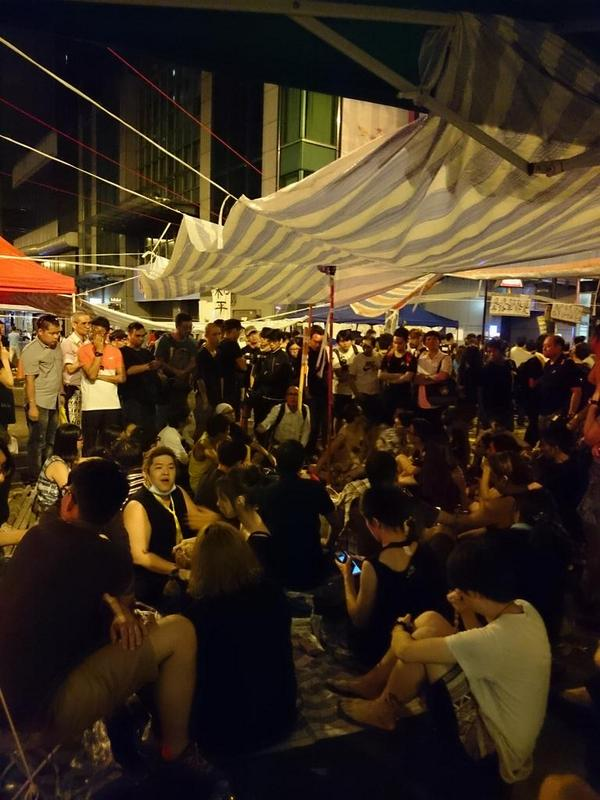 In HongKong's Mong Kok district, occupiers huddle around to talk politics at 5:09am