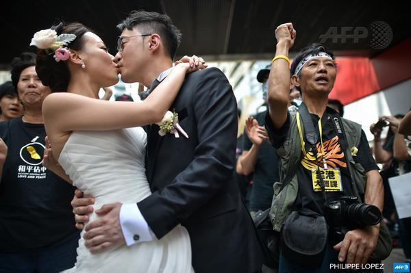 A couple takes wedding photographs in front of protest