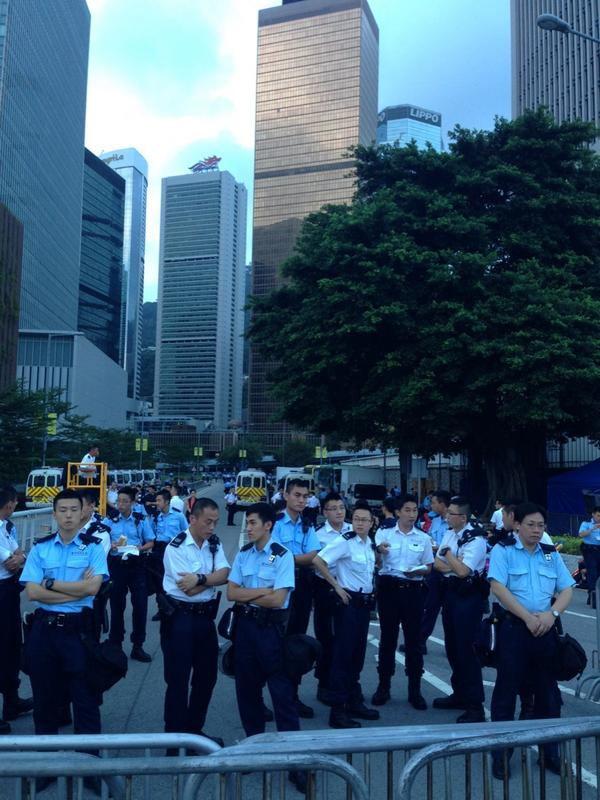 White shirted senior police officers take stock in meeting at the barricades outside CY's office occupycentral