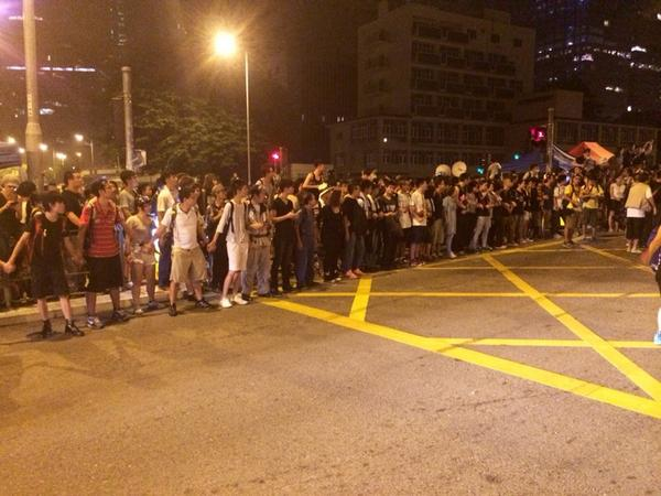 Anti-road block demonstrators have now linked arms and formed a wall to stop others from joining roadblock.