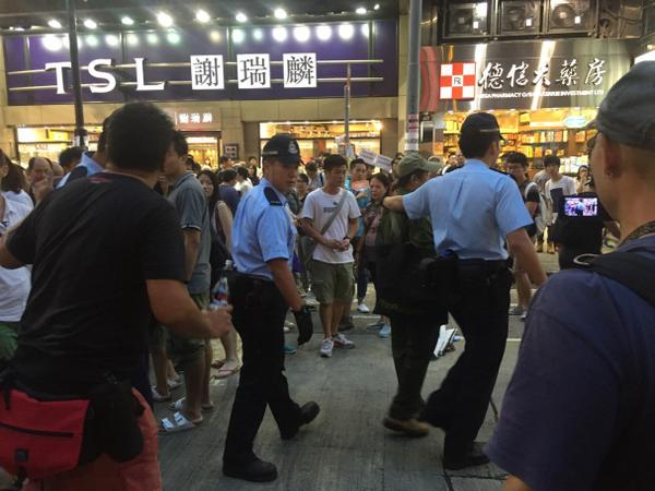 Police escort one man away. Lots of curious onlookers hongkong