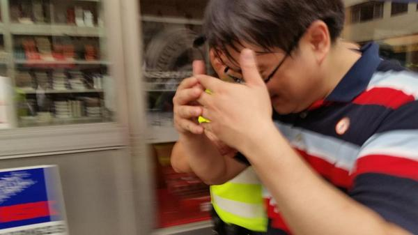Man caught carrying scissors and cutting plastic security strips on barricades is taken away by police in Mongkok
