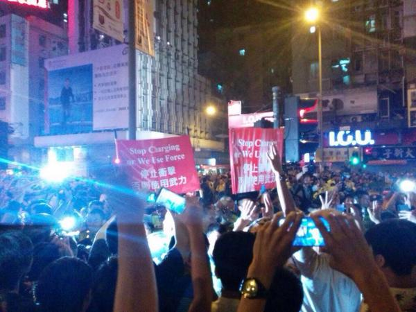 OccupyHK demonstrators put their hands up after police raise Stop charging or we will use force signs in Mongkok.