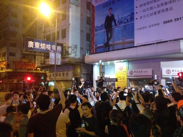Офіцер поліції робить заяви, але дуже погано чути. Він закликає громадян зберігати спокій.