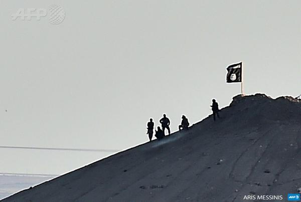 Alleged ISIS militants stand next to their flag atop a hill in the Syrian Kurdish town of Kobane
