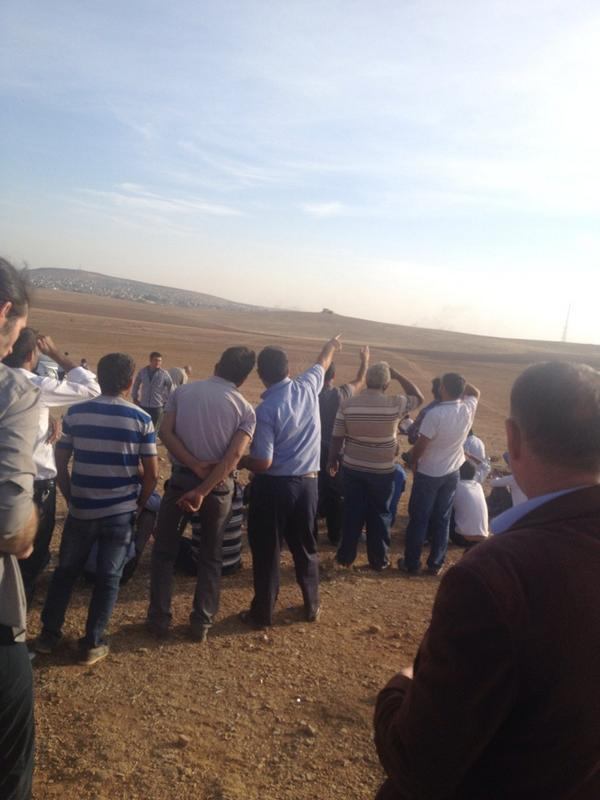 Plane is back over Kobane. Crowd on Turkish side trying to spot it. Young & old all gathered to watch