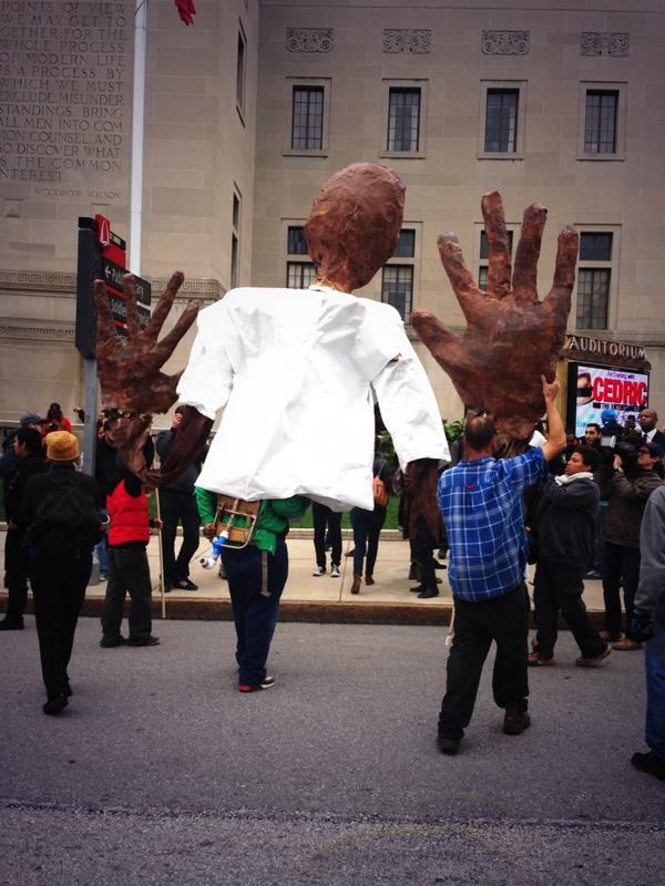 Giant paper mache of a black man with his hands up. MichaelBrown