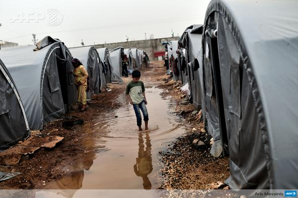 A Syrian Kurdish refugees walks through a camp in Suruc, Turkey, after fleeing the besieged town of Kobane