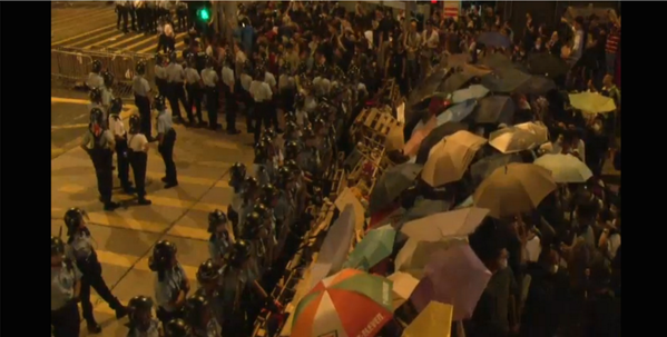 Umbrellas and the black helmets of riot police have become familiar scenes