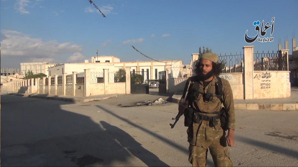 Islamic state soldier in front of the Cultural center of Kobane
