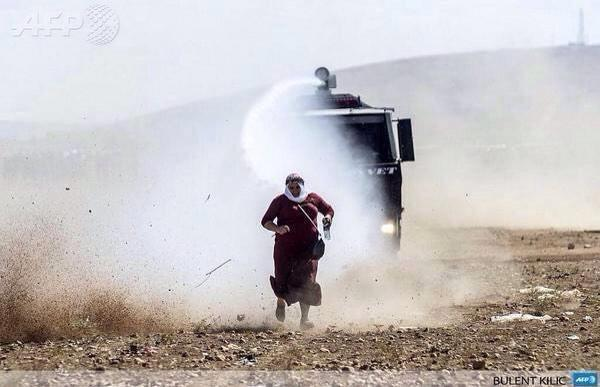 A Kurdish Grandmother being chased by Turkish police while she is at the border of Kobane 2 support her children