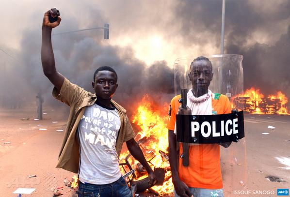 BurkinaFaso: Protesters stand outside parliament in Ouagadougou as cars & documents burn.