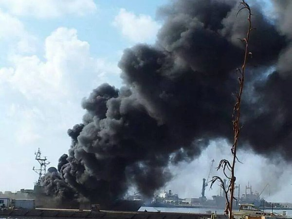 Smoke rises from a shelled ship docked in the port of Benghazi. due to clashes between AAS militias & army Libya