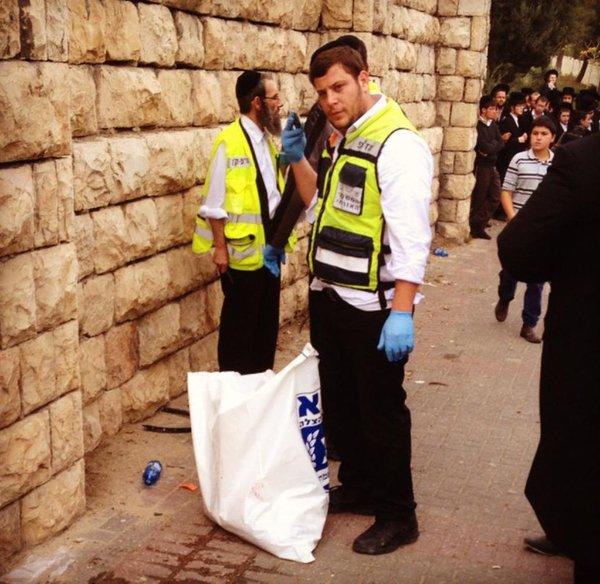 Zaka volunteers cleaning the blood o/s of todays Jerusalem car terrorist attack, 1 dead, 10 wounded.