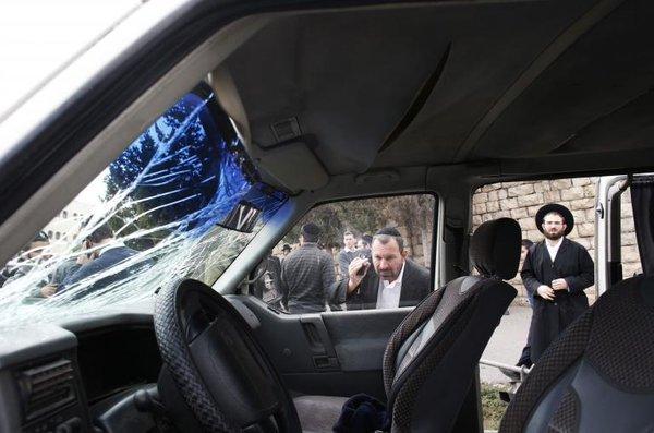 Ultra-Orthodox Jewish man looks at vehicle of Palestinian motorist who drove into pedestrians in Jerusalem