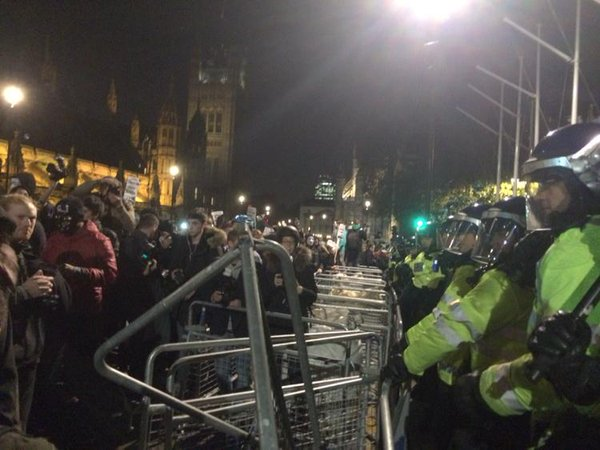 In front of the houses of Parliament in London police behind barricade from protestors at MillionMaskMarch
