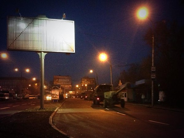 Convoy of artillery, trucks rolling casually thru central Donetsk