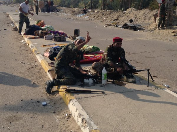 Fighters from volunteer militia clean their weapons on Fadhiliyah Bridge in Iraq.