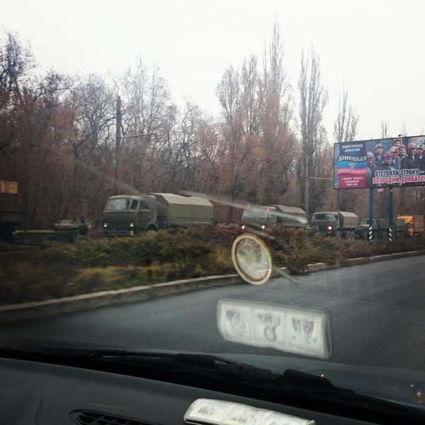 Another convoy of about a dozen military trucks with attached howitzers is waiting on the E entrance to Donetsk