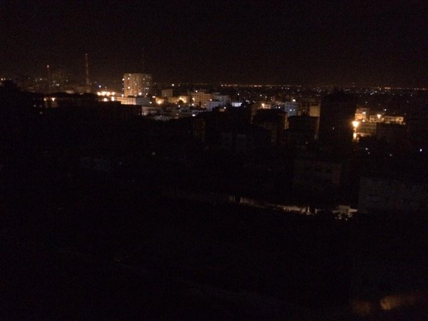 Gaza City is densely built around me but the electricity is out. The furthest row of lights are Israeli communities.