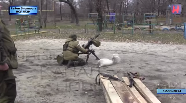 Putin's militants firing an automatic grenade launcher  at Ukrainian Checkpoint 29 from childrens playground.