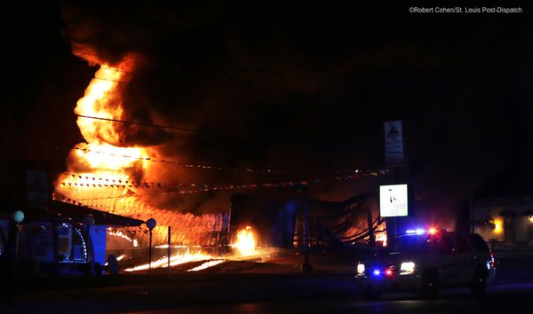 Ferguson police passes a burning AutoZone on West Florissant.